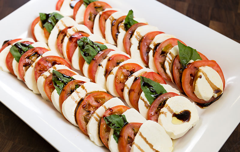 caprese saladwith fresh mozzarella, roma tomatoes, basil, olive oil and balsamic glaze