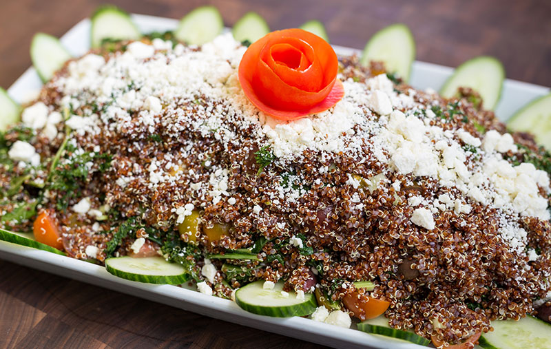 red quinoa and kale saladwith quinoa, baby greens, tomatoes, cucumbers, celery, olives, greens onions, feta cheese and lemon citronette